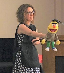 Gwyn presenting practical training holding a puppet on a selfie stick