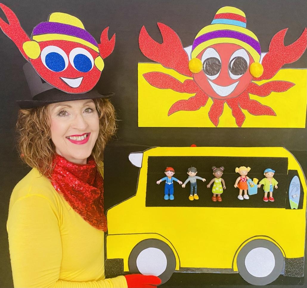 Gwynnie-Gwyn-Gwyn the story teller holding the yellow school bus with the Little Friends on board. Gwynnie-Gwyn-Gwyn is wearing the Crazy Crab Craig hat and the character Crazy Crab Craig is on the wall behind the bus.